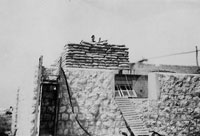 soldier peering over sandbagged barricade on roof