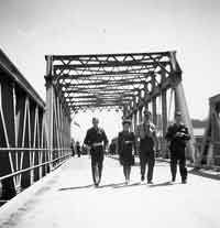 3 men and 1 woman in uniform crossing a bridge.