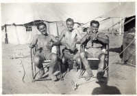 3 soldiers sitting outside their tents and eating grapes