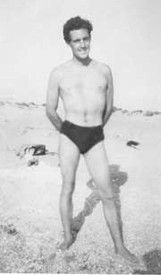 handsome young man in bathing trunks standing on a beach.