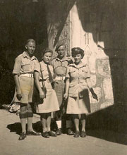 2 young men and 2 young women in uniform standing by a stone wall.
