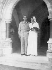 wedding couple standing under the stone arch of a church porch.