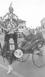 two soldiers in rickshaw pulled by highly decorated zulu