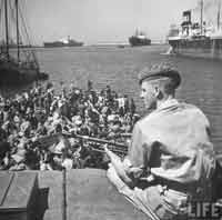 soldier  on guard on ship with refugees